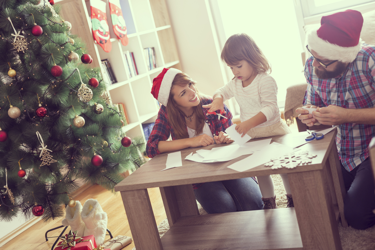 Mother, father and daughter sitting on a living room floor, cutting paper snowflakes and enjoying winter holidays together. Focus on the mother