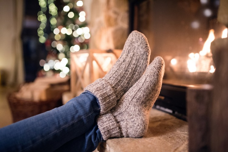 Feet of unrecognizable woman in woollen socks by the Christmas fireplace. Winter and Christmas holidays concept.