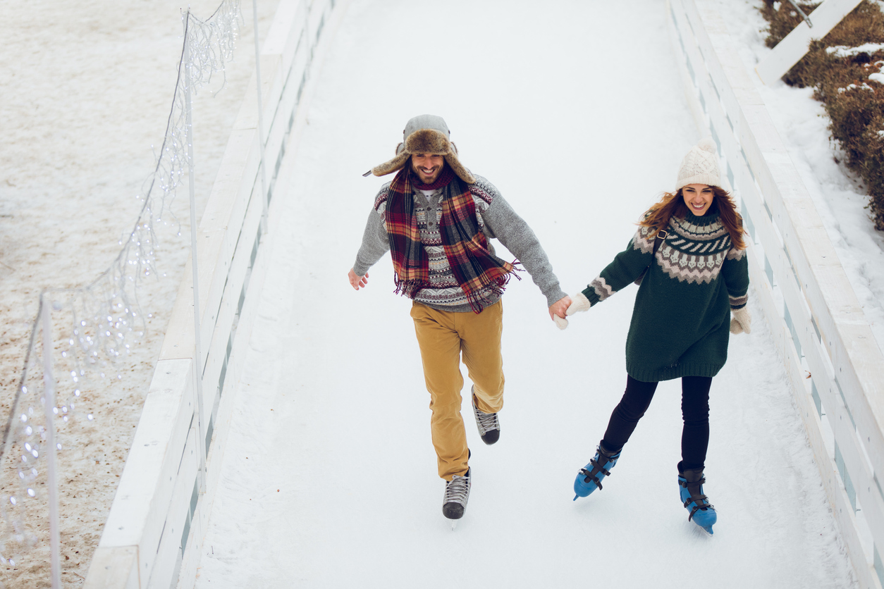 Romantic couple skating together in ice rink holding hands. High angle view.
